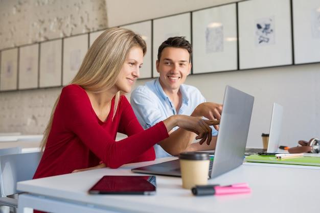 オープンスペースの共同作業事務室でラップトップに取り組んでいる現代の若い男性と女性