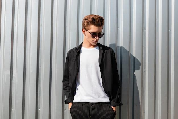우아한 최신 유행의 옷에 세련된 선글라스에 헤어 스타일을 가진 현대 젊은이 hipster 거리에서 빈티지 금속 벽 근처 이완. 매력적인 남자는 화창한 여름 날에 휴식을 즐깁니다.