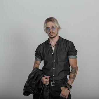 빈티지 벽 근처 스튜디오에서 포즈 라운드 안경 재킷과 검은 유행 옷에 문신과 현대 젊은 남자 힙 스터