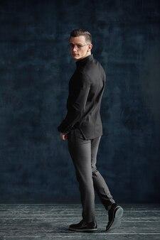 Современный молодой человек в полный рост. уверенный молодой человек позирует перед камерой в студии лофта.