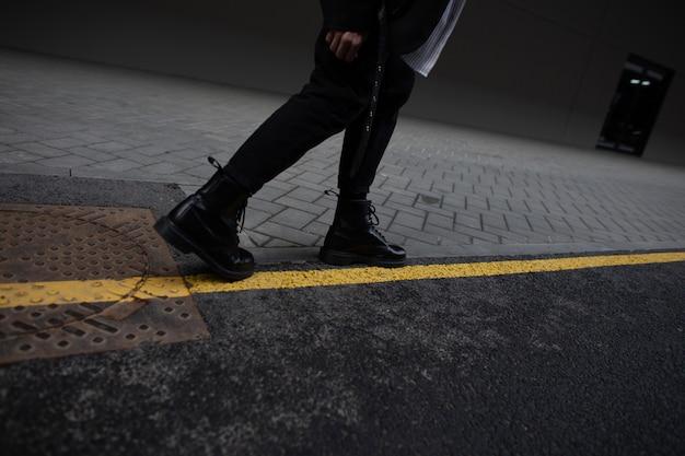 ファッショナブルな革の春のブーツでスタイリッシュな黒のズボンを着た現代の若い男は、黄色の線で道路上の街に立っています。若者のモダンなヴィンテージの靴のクローズアップでトレンディな男性の足。詳細