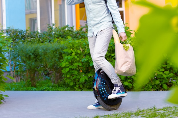 Modern young man male guy successful student freelancer entrepreneur with package of food vegatebles and fruits with eco electric transport / balancing wheel / electric unicycle outdoor going home
