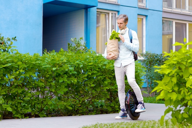 Modern young man male guy successful student freelancer entrepreneur with package of food vegatebles and fruits with eco electric transport / balancing wheel / electric unicycle outdoor going home Premium Photo
