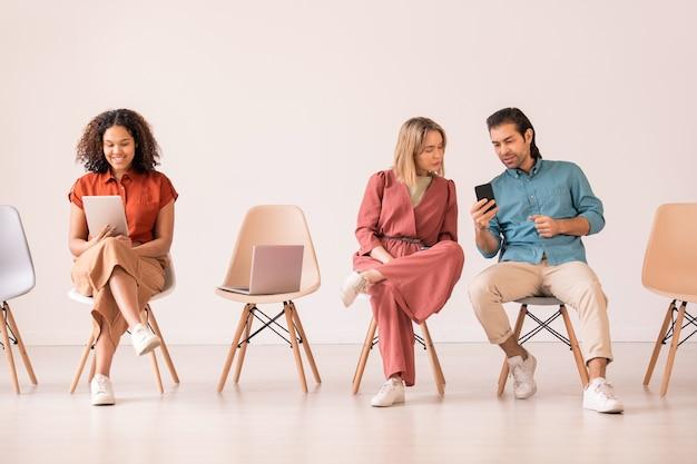 Современный молодой человек показывает девушке новое удобное приложение для смартфона, пока темнокожая женщина разговаривает через видеочат на планшете