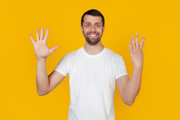 白いタンクトップにひげを生やした現代の若い男は、カメラを見て自信を持って幸せに笑っている手に指を持った9番を示しています。
