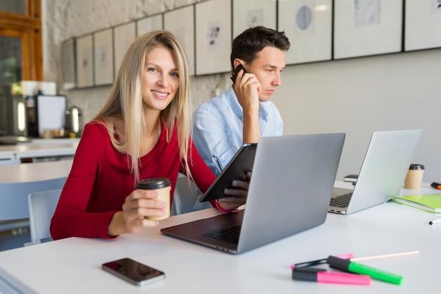 Giovane moderno e donna che lavorano al computer portatile nella stanza dell'ufficio di co-working dello spazio aperto