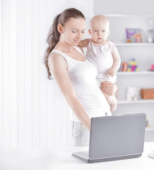 보육원에서 매력적인 아기와 함께 현대 젊은 어머니