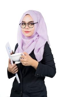 コーヒーカップとフォルダーを保持している現代の若いイスラム教徒の女性