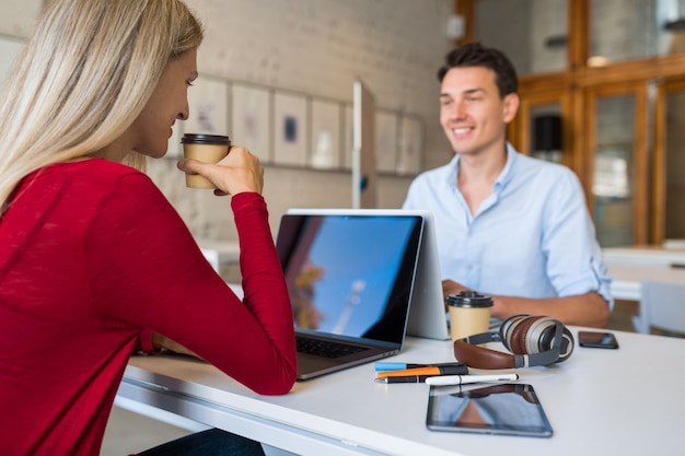 Giovani moderni seduti a tavola faccia a faccia, lavorando al computer portatile in ufficio di co-working