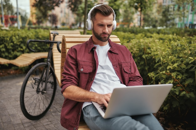 Modern and young portrait of handsome man with stubble in casual clothes listening music and