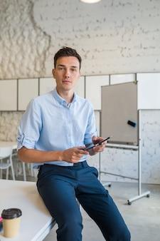 Современный молодой стильный улыбающийся человек в коворкинг-офисе, фрилансер запуска, держащийся с помощью планшета,
