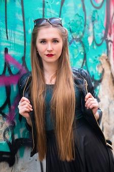 Modern young woman next to graffiti wall