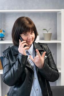 바이커 재킷을 입은 현대 젊은 여성이 전화 통화를 하고 경적 손짓을 합니다. 여자는 데이트를 한다.