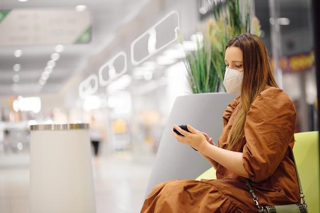 保護マスクの現代の若い女性はショッピングセンターを休んでいて、スマートフォンを見ています