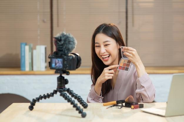 Современная молодая женщина-влиятельный человек демонстрирует свою повседневную косметику во время разговора на камеру дома. азиатская бьюти-блогерша вела прямую трансляцию, чтобы рассказать о косметике в социальных сетях