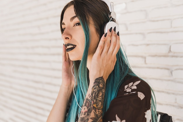 Modern young woman listening music on headphone