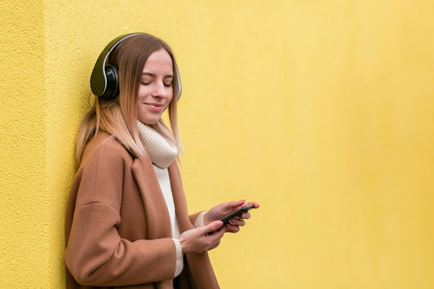 Modern young woman listening to music on headphones with copy space