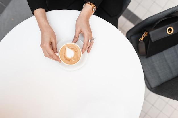 現代の若い女性は、カフェのヴィンテージの白いテーブルに座って、ホットでおいしいカプチーノのカップを持っています。女性の手でコーヒーとテーブルの上面図。