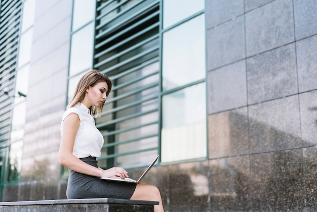 Modern young woman sitting outside the building using laptop