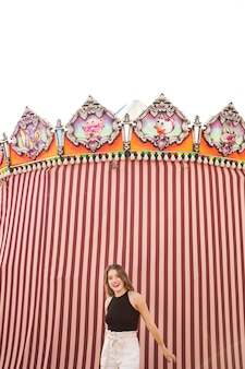Modern young woman standing in front of decorative tent