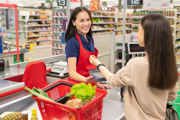 Modern young woman using smart watch technology to pay for goods in modern supermarket