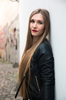 Modern young woman next to white wall