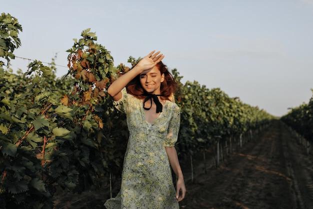 Современная молодая женщина с красной прической и черной повязкой на шее в летнем стильном платье улыбается и позирует на виноградниках