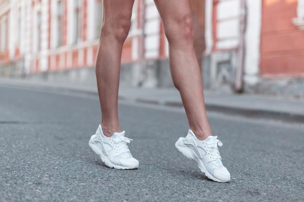 세련된 흰색 운동화에 날씬한 아름다운 다리를 가진 현대 젊은 여성이 거리를 산책합니다. 세련된 스포티 한 여성 신발. 여름 스타일. 신발 여성 다리의 근접 촬영입니다.