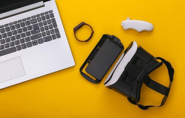 Современные молодежные гаджеты и устройства на желтом фоне. вид сверху. плоская планировка