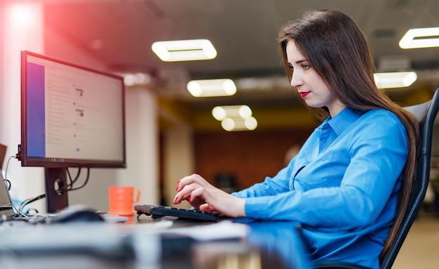 Разработчик программного обеспечения, работающий за компьютером на modernfice. красивая молодая женщина, программирование, разработка технологий в ит-компании. высокое качество изображения.