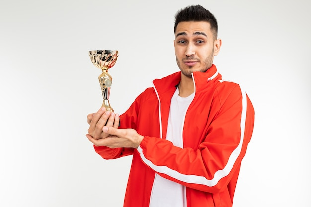 Modest athlete in a tracksuit with a golden winner cup on a white studio background.