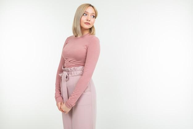 Скромная блондинка в розовой блузке мило улыбается с копией пространства