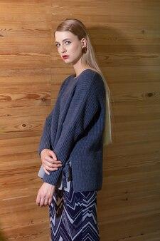 セーターとウールのスカートの木製の壁でポーズをとる控えめな白人金髪の若い女性。