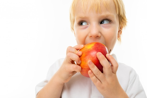 Modest charming blonde child dressed in a white t-shirt eats an apple on a white wall with copy space