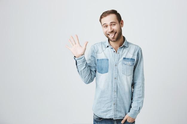 Modesto uomo barbuto carino saluta, agitando la mano in segno di saluto, mostra la lingua