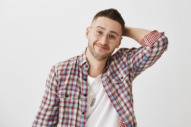眼鏡ポーズの控えめなハンサムな笑顔の若い男