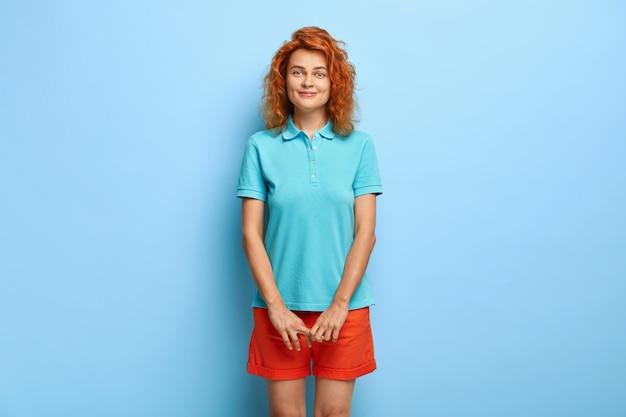 ウェーブのかかった赤い髪の控えめな素敵な10代の少女は、表情を満足させ、カジュアルな青いtシャツとショートパンツを着ています