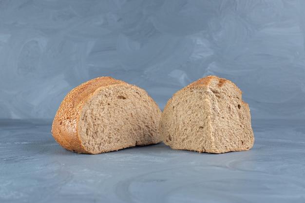 Modeste fette di pane ricoperto di sesamo sul tavolo di marmo.