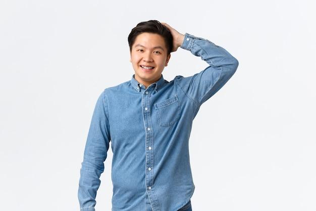 控えめな笑顔のアジア人男性、善行をするように赤面し、頭をかきむしり、混乱し、ぎこちなく、白い背景の上にかわいい立っています。きれいな女性と話しているナイスガイ。コピースペース