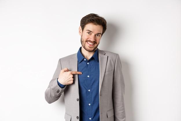 スーツを着た控えめな笑顔の男がかわいい顔で自分自身を指して、自己宣伝し、白い背景の上に立っています。