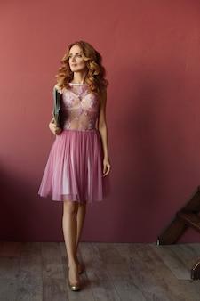 Модная стройная модель девушки в розовом коктейльном платье, ведёт журнал и позирует в салоне.