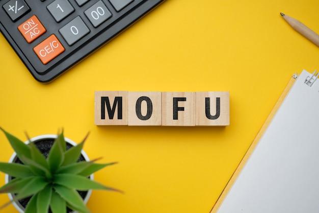 現代のマーケティング流行語-mofu middle of funnel。ブロックと木製のテーブルの上から見る。上面図。