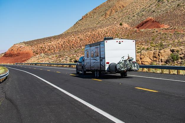 66번 국도 옆 모하비 사막. rv 캠핑, 도로 위의 캠퍼 밴. 미국의 산악 도로에 있는 캐러밴 또는 레저용 차량 모터 홈 트레일러.