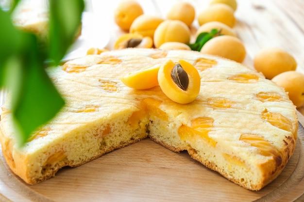背景にアプリコットフルーツと木の板の湿ったアプリコットパイ。おいしい朝食、伝統的なイングリッシュティータイム。古典的なレシピによる自家製ベーカリー。健康的な栄養、ビーガンデザート。