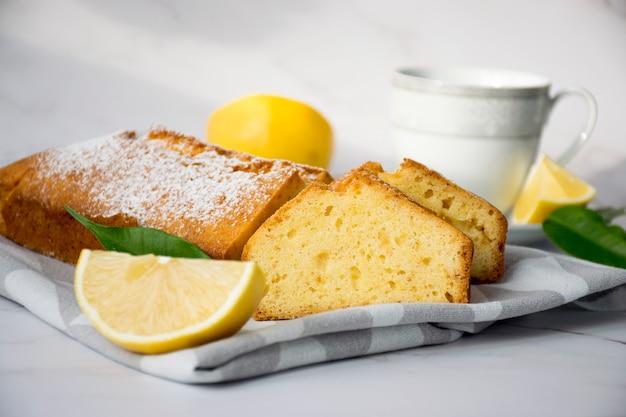 레몬 조각과 접시에 차 한잔과 대리석 테이블에 주방 수건에 촉촉한 레몬 파운드 케이크. 맛있는 아침 식사, 전통 차 시간 치료. 영어 레몬 파이 덩어리의 요리법.
