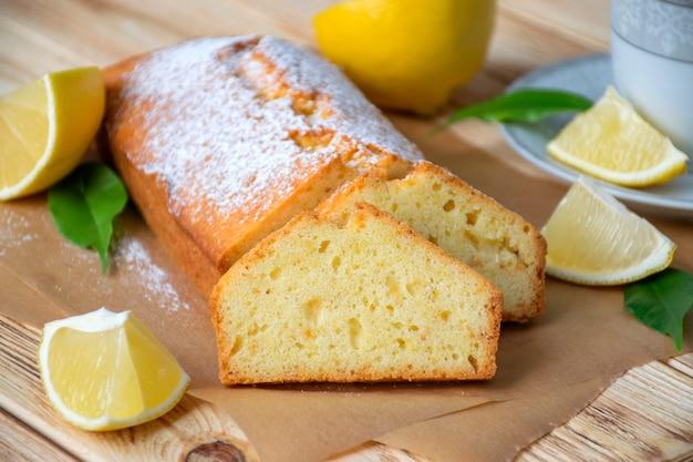 Влажный лимонный пирог на пергаменте на деревенском деревянном фоне с кусочками лимона и чашкой чая на тарелке. вкусный завтрак, традиционное угощение к чаю. рецепе английского лимонного пирога.