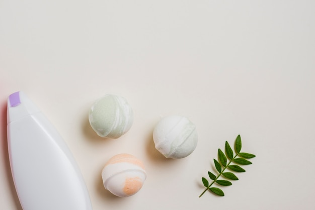 Moisturizer bottle; bath bombs and leaves on white background