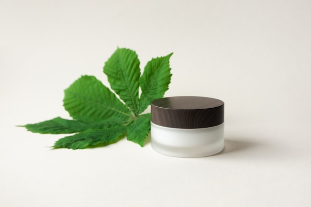 Moisturizer cream or body lotion in frosted glass jar with wooden cup and horse chestnut leaf on beige table