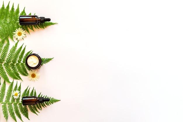 保湿クリームジャー、シダの葉と白い背景の上のガラス瓶の血清。スキンケアとボディケアの美容製品用に設定されています。ブランド化されていないパッケージ