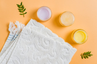 Moisturizer cream with white towel on colored background